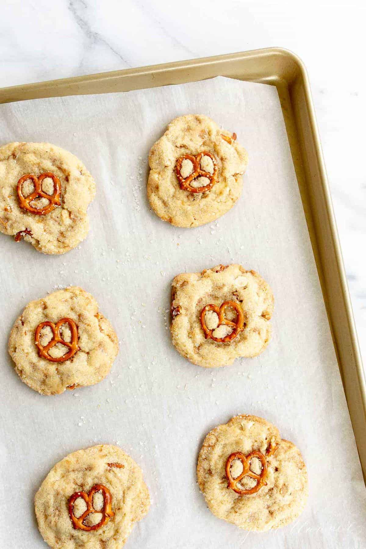 Gold baking sheet lined with parchment paper, white chocolate chip cookies topped with pretzel on top.