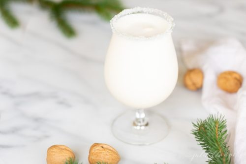 Marble surface with a clear glass filled with a snowball drink, rimmed in sugar, with chestnuts and evergreen touches around.