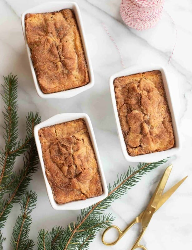 Marble surface with 3 loaves of cinnamon bread, evergreen and scissors to the side.