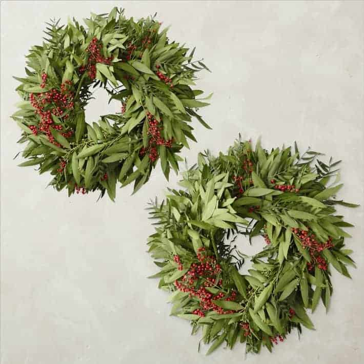 product shot of two bay leaf and pepperberry holiday wreaths.