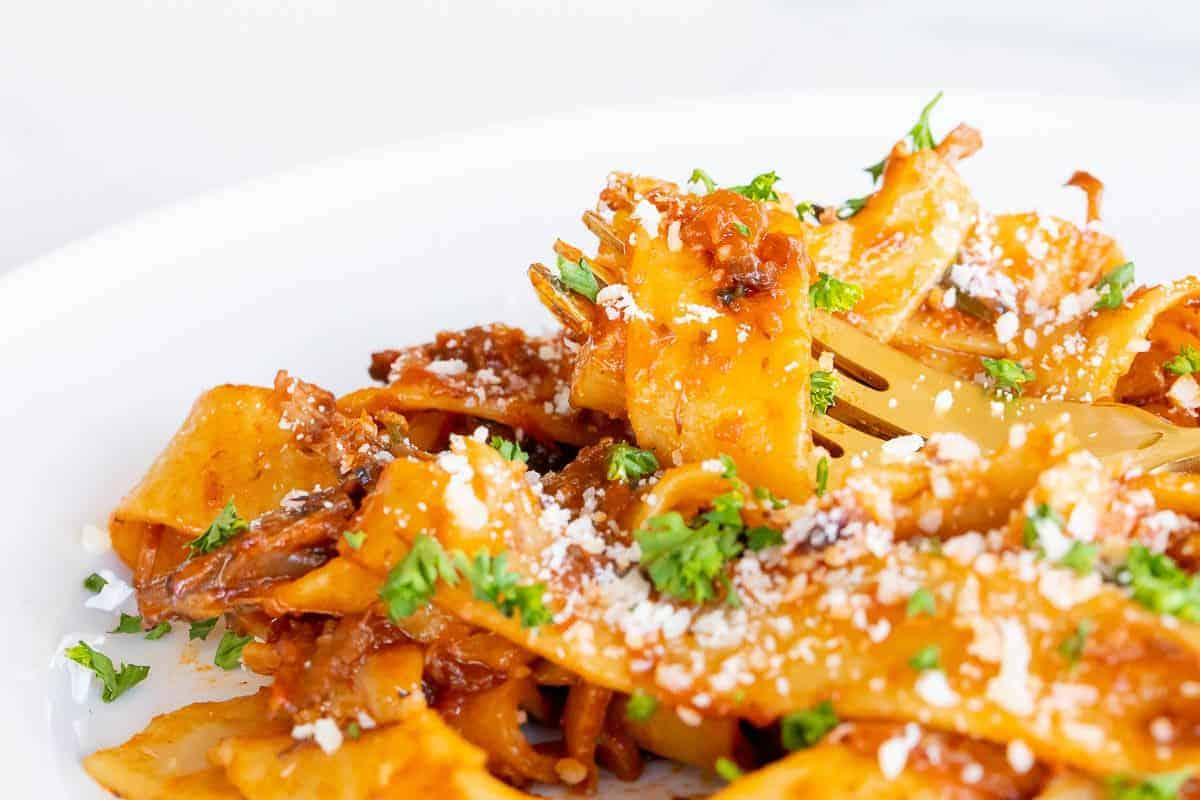 A small white plate with beef ragu and pappardelle pasta, gold fork to the side.
