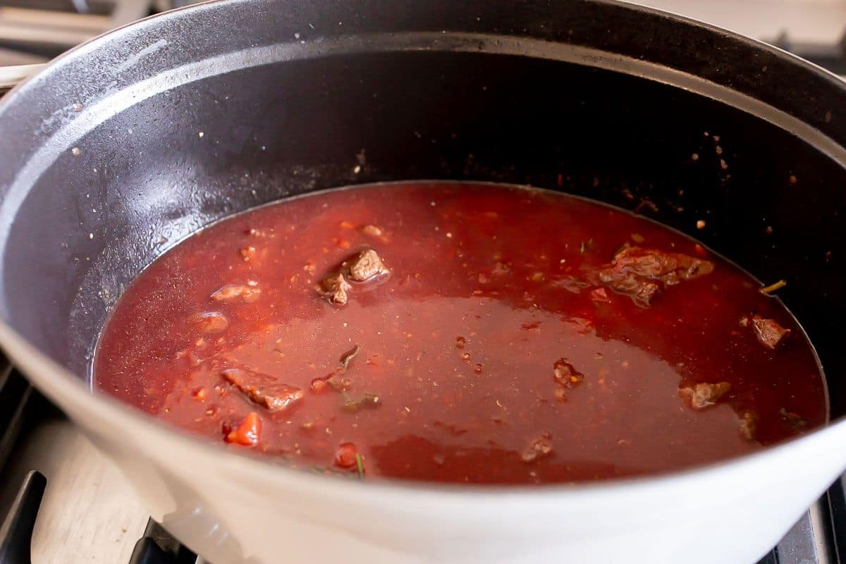 A white cast iron pot on a stove, filled with beef ragu sauce simmering.