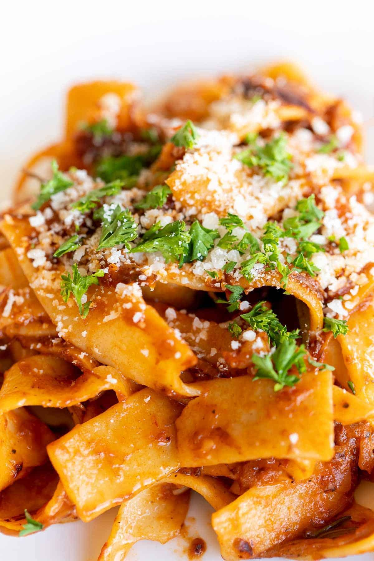 A close up of pappardalle pasta with beef ragu sauce, topped with parsley and parmesan.
