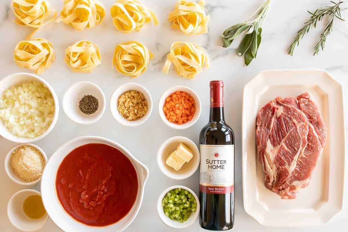 Ingredients for a beef ragu recipe laid out on a white marble surface.