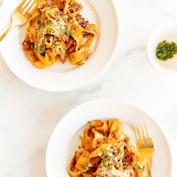 Two white plates on a marble surface, filled with a beef ragu recipe and a small bowl of parsley to the side.