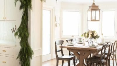 traditional kitchen draped in garland peeking into breakfast nook with blue christmas flower arrangement
