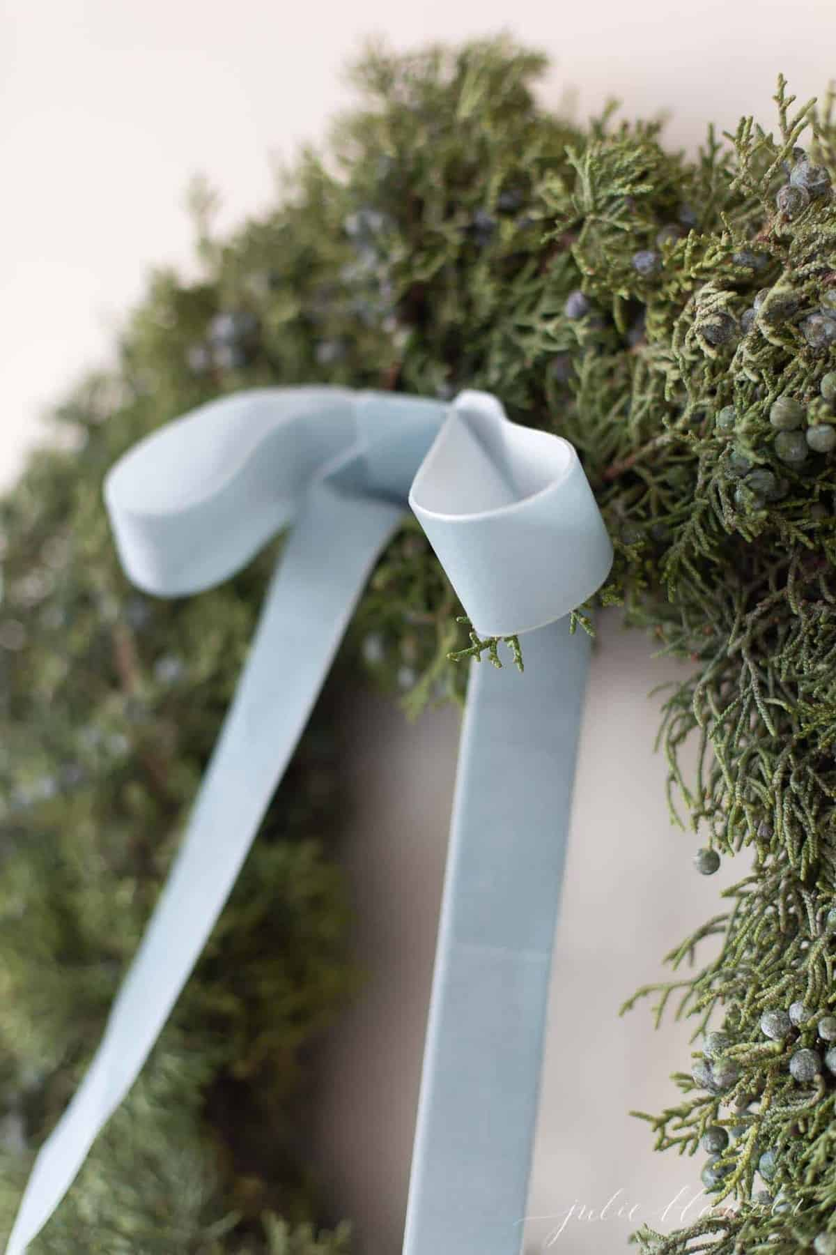 Close-up of a juniper wreath with a velvet wreath for blue Christmas decorations.