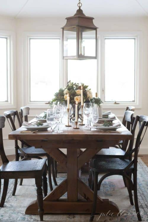 Dining room with wooden table and chairs set with a blue christmas table setting.