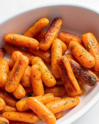 White oval serving platter with roasted dill carrots.