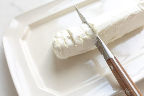 White platter with a log of chevre cheese, knife slices into it.