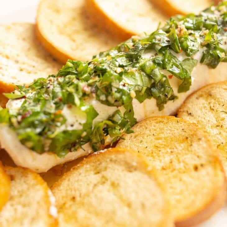 A goat cheese appetizer with a single log of chevre cheese, marinated in herbs and oil, crostini to the side.