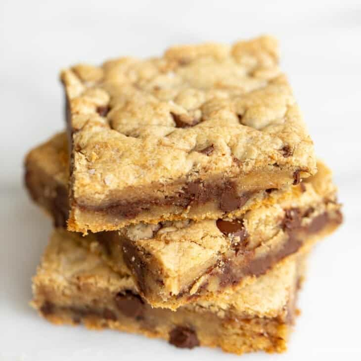 Stack of three cookie bars with chocolate chips and salted caramel.