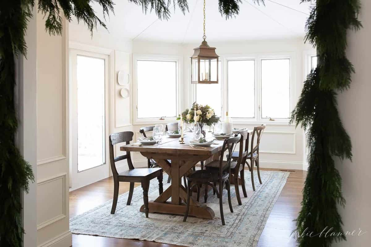 christmas table setting in a breakfast nook draped in cedar garland