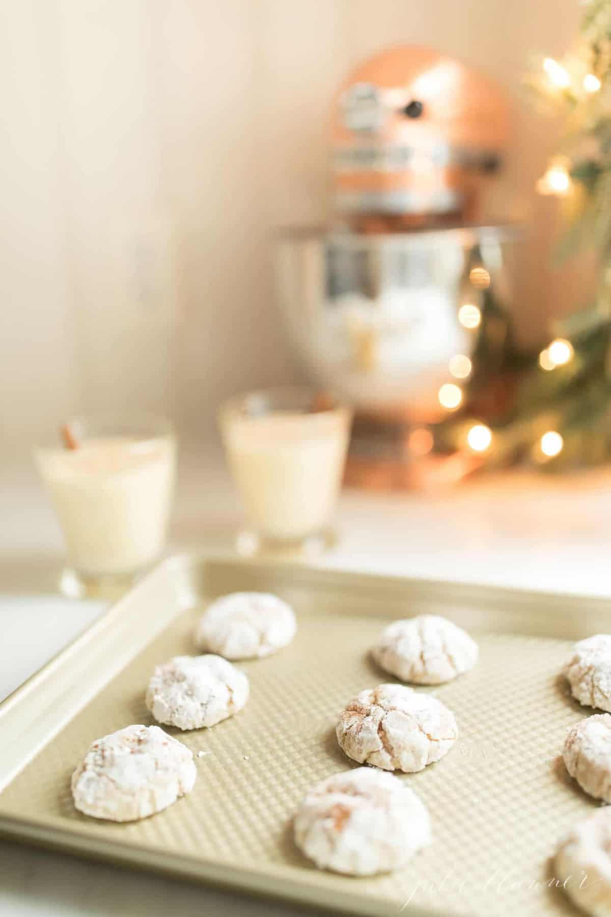 eggnog cookies covered in powdered sugar on baking sheet next to two cups of eggnog a mixer and prelit garland