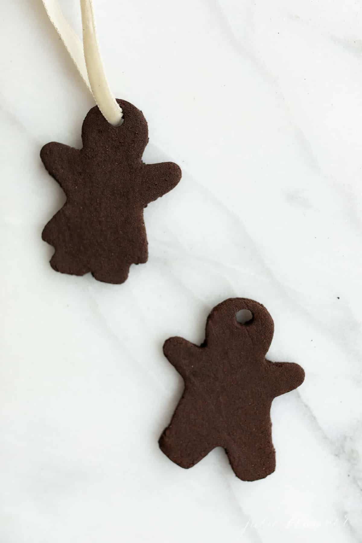 Two gingerbread cutout cinnamon applesauce ornaments on a marble surface.
