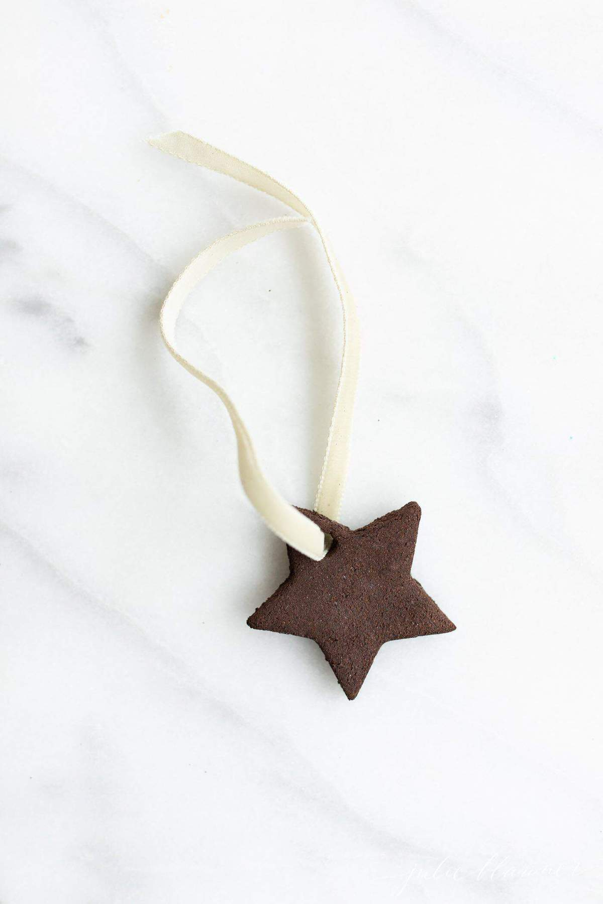 A single star handmade ornament on a marble surface.