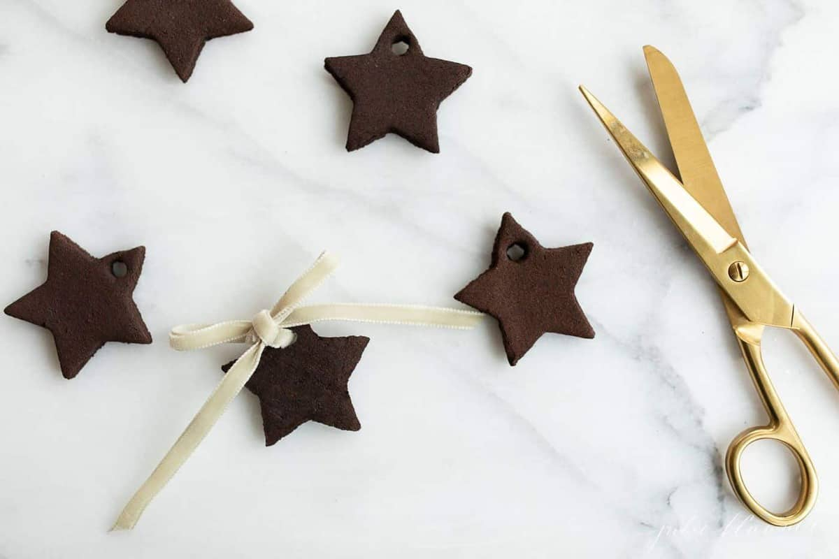 Cinnamon ornaments in the shape of stars on a marble surface, gold scissors to the side