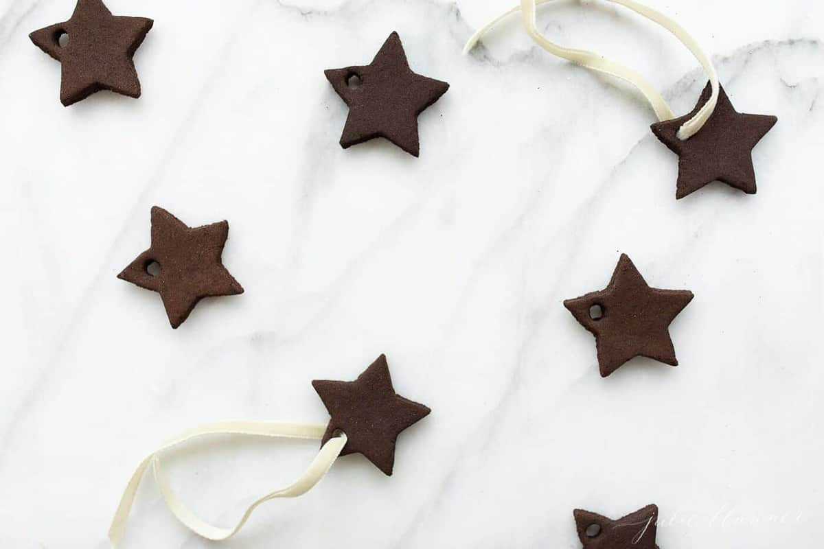 Cinnamon ornaments in the shape of stars on a marble surface.