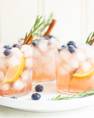 Three Smash cocktails garnished with rosemary, blueberries, oranges, and cinnamon sticks all on a white plate.