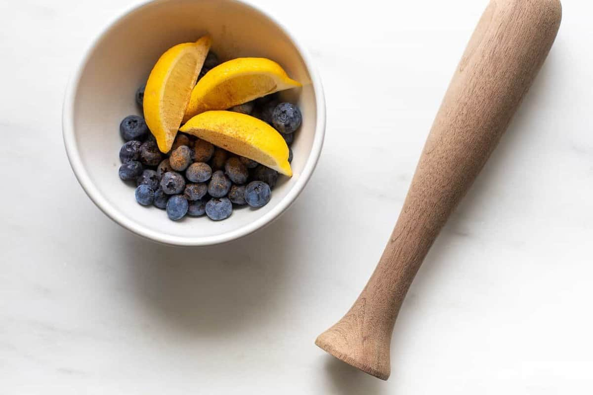marble surface, bowl of lemon slices and blueberries with a wooden muddler.