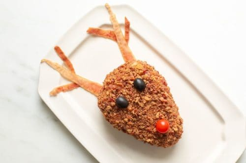 White platter with a cheddar cheese ball in the shape of a reindeer.
