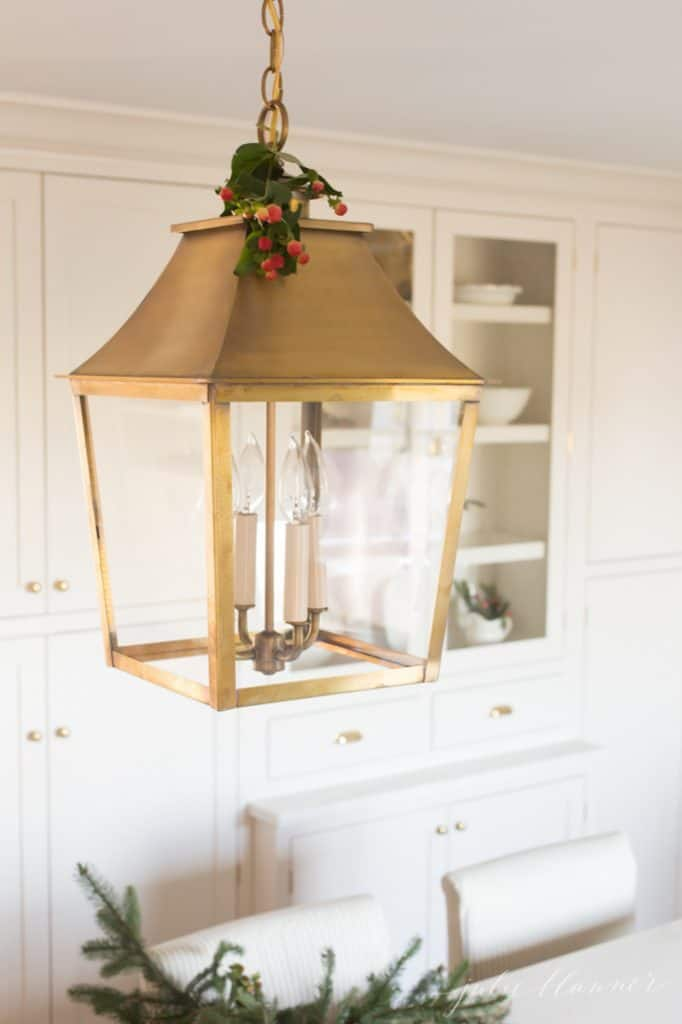 A brass lantern in a white kitchen decorated with a touch of greenery for Christmas decorations.