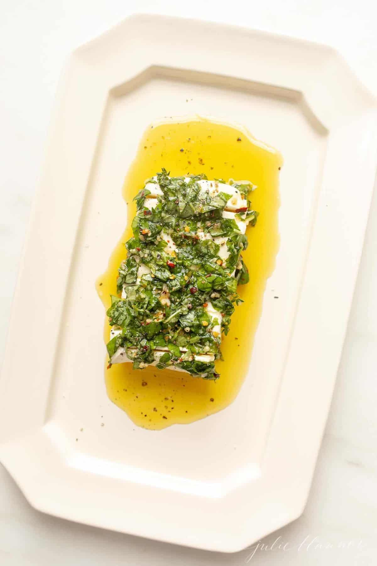 White platter with a cream cheese appetizer, marinated cheese recipe in herbs and oil.