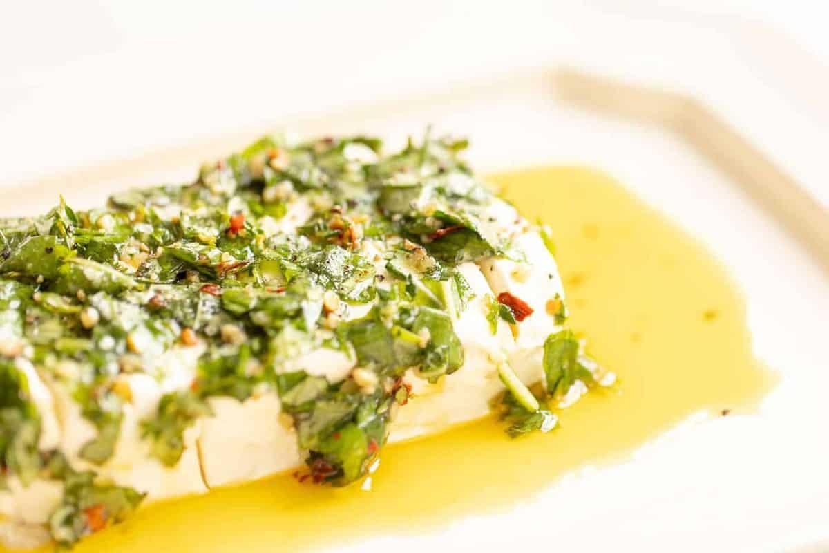 Prato branco com aperitivo de cream cheese, receita de queijo marinado com ervas e óleo.