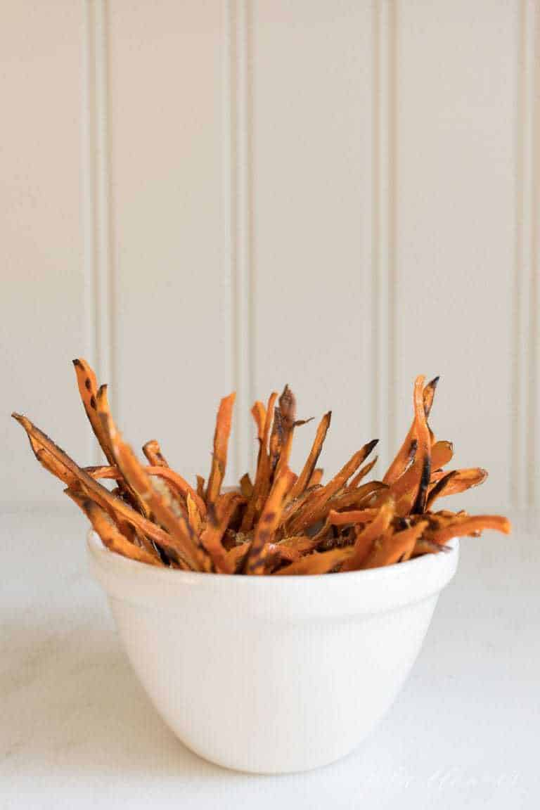 A white surface with a white bowl of baked sweet potato fries.