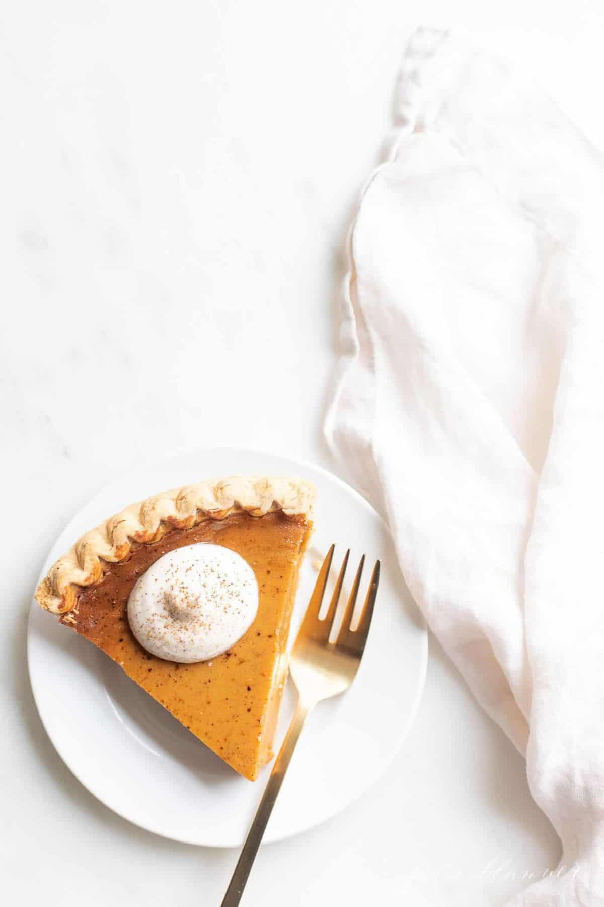 A slice of pumpkin pie with a dollop of whipped cream, placed on a white plate, gold fork and napkin to the side.