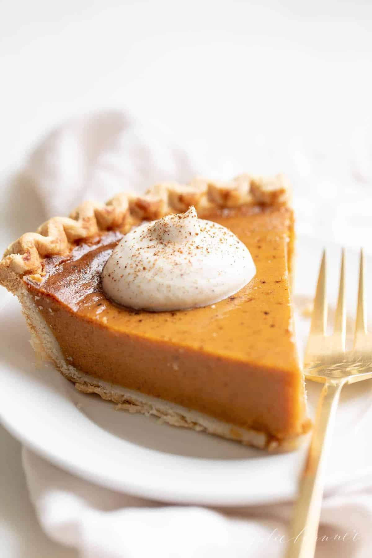 A slice of pumpkin pie with a dollop of eggnog whipped cream, placed on a white plate, gold fork to the side.