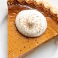 A slice of pumpkin pie with a dollop of eggnog whipped cream, placed on a white plate.