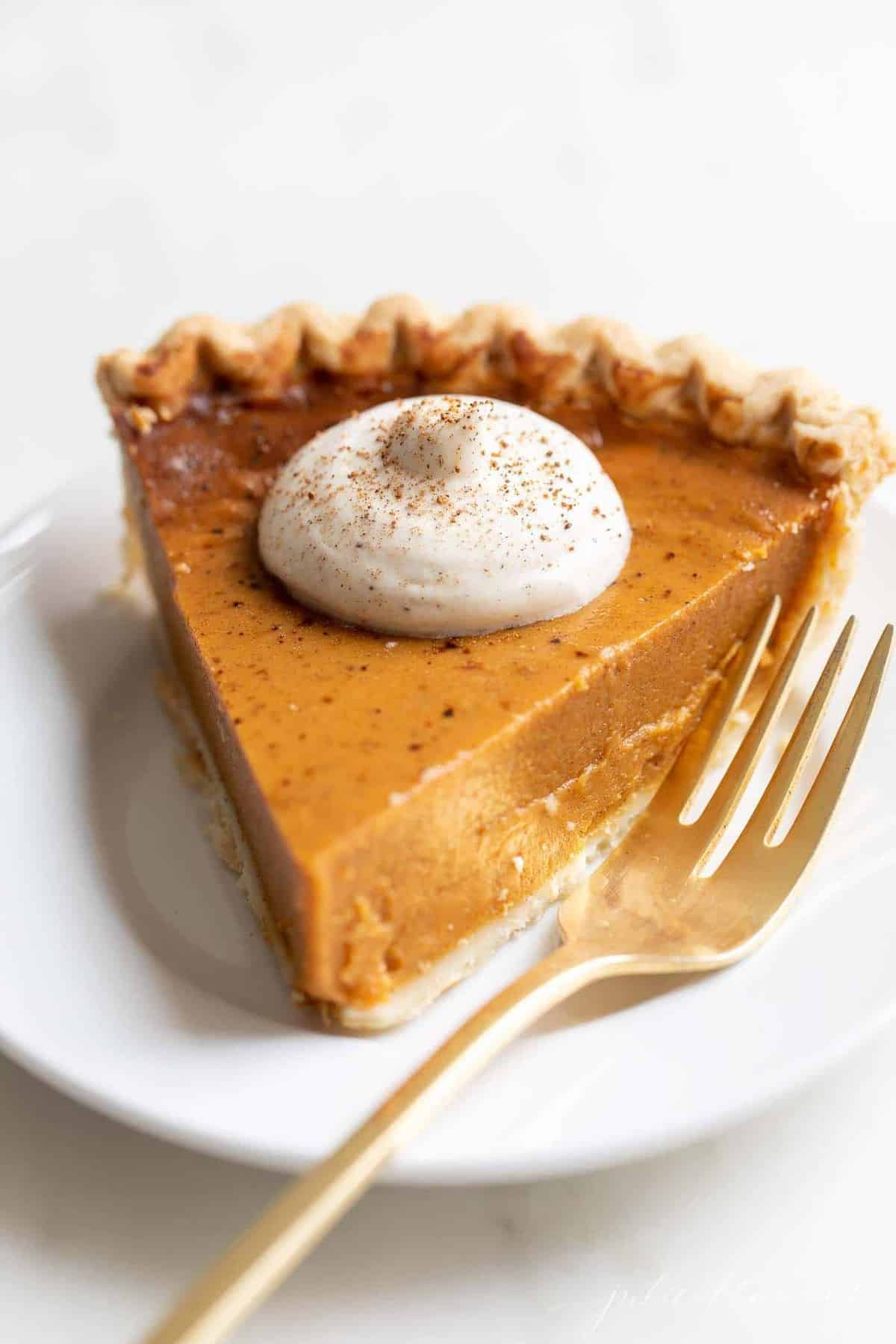 A slice of pumpkin pie with a dollop of spiced whipped cream, placed on a white plate, gold fork to the side.