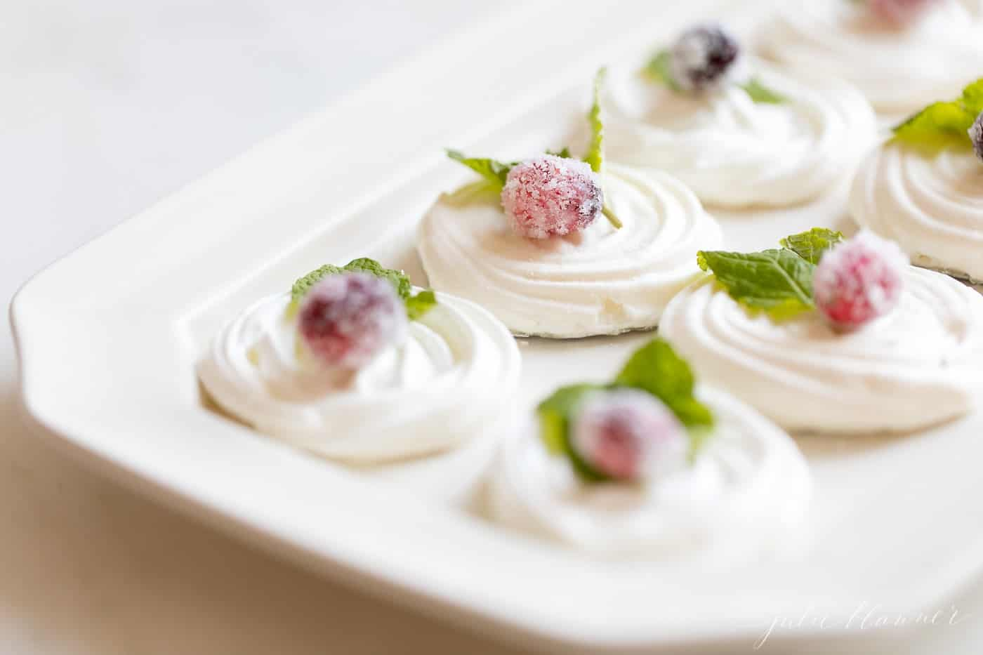 meringues decorated with sugared cranberries and mint leaves on a platter