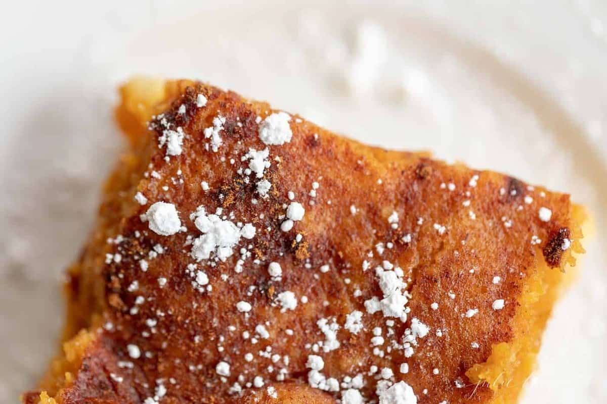 close up of a slice of pumpkin gooey butter cake sprinkled with powder sugar.