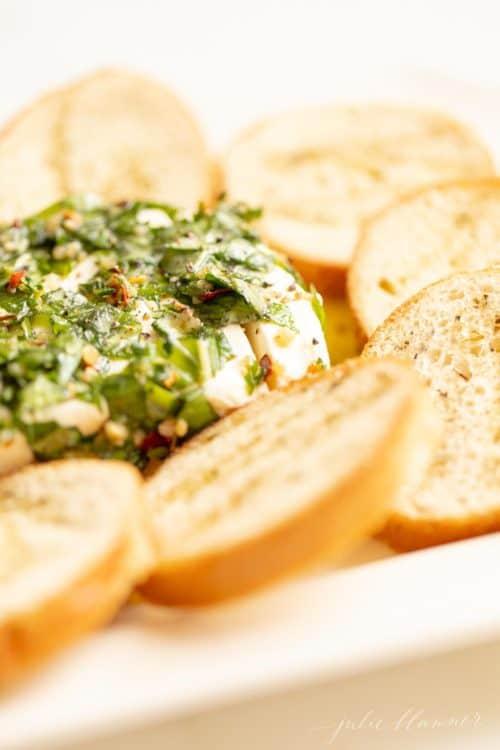 Um aperitivo de cream cheese com receita de cream cheese marinado em ervas e óleo, crostini ao lado.