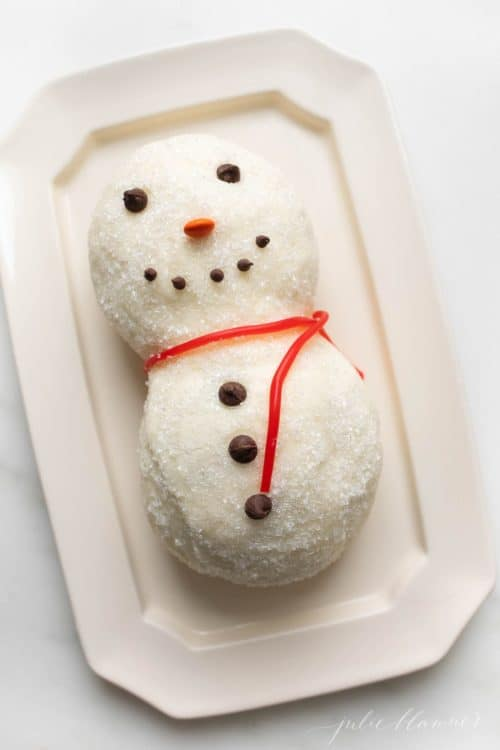 A sugared snowman cheese ball recipe, licorice for scarf on a white platter.
