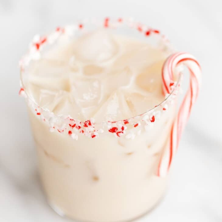 Marble surface with a peppermint white russian, candy cane garnish.