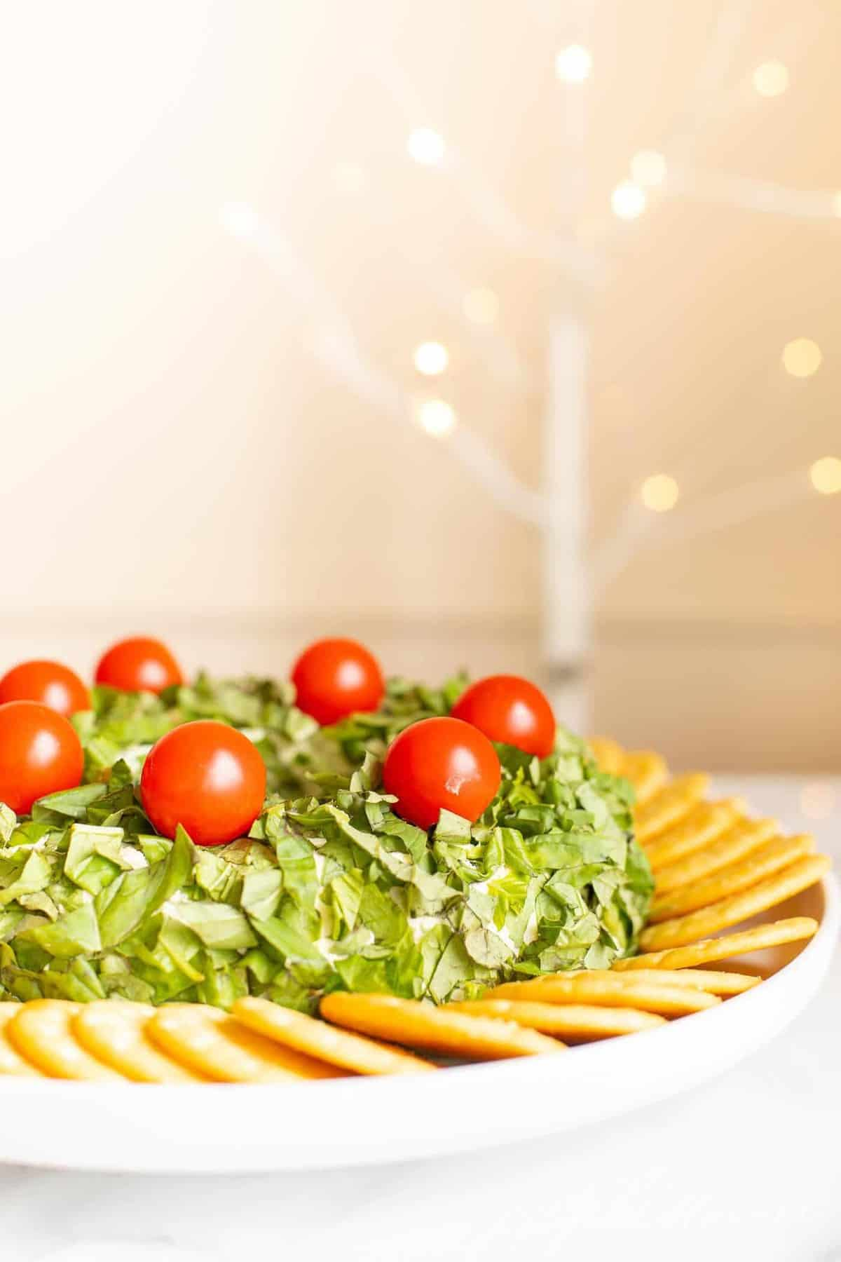 A pesto cheeseball Christmas wreath appetizer surrounded by crackers on a platter.