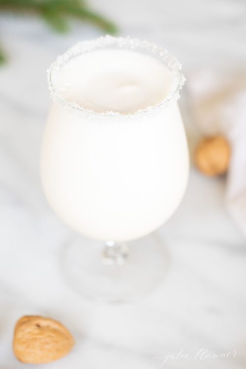 Marble surface with a clear glass filled with a snowball cocktail, rimmed in sugar, with chestnuts tossed around.