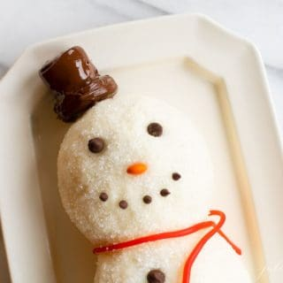 White surface, snowman cheeseball on a platter, chocolate chip smile.