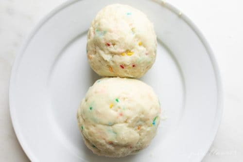 Two balls of no bake dessert cheeseball on a white plate, learn how to make a cheeseball.
