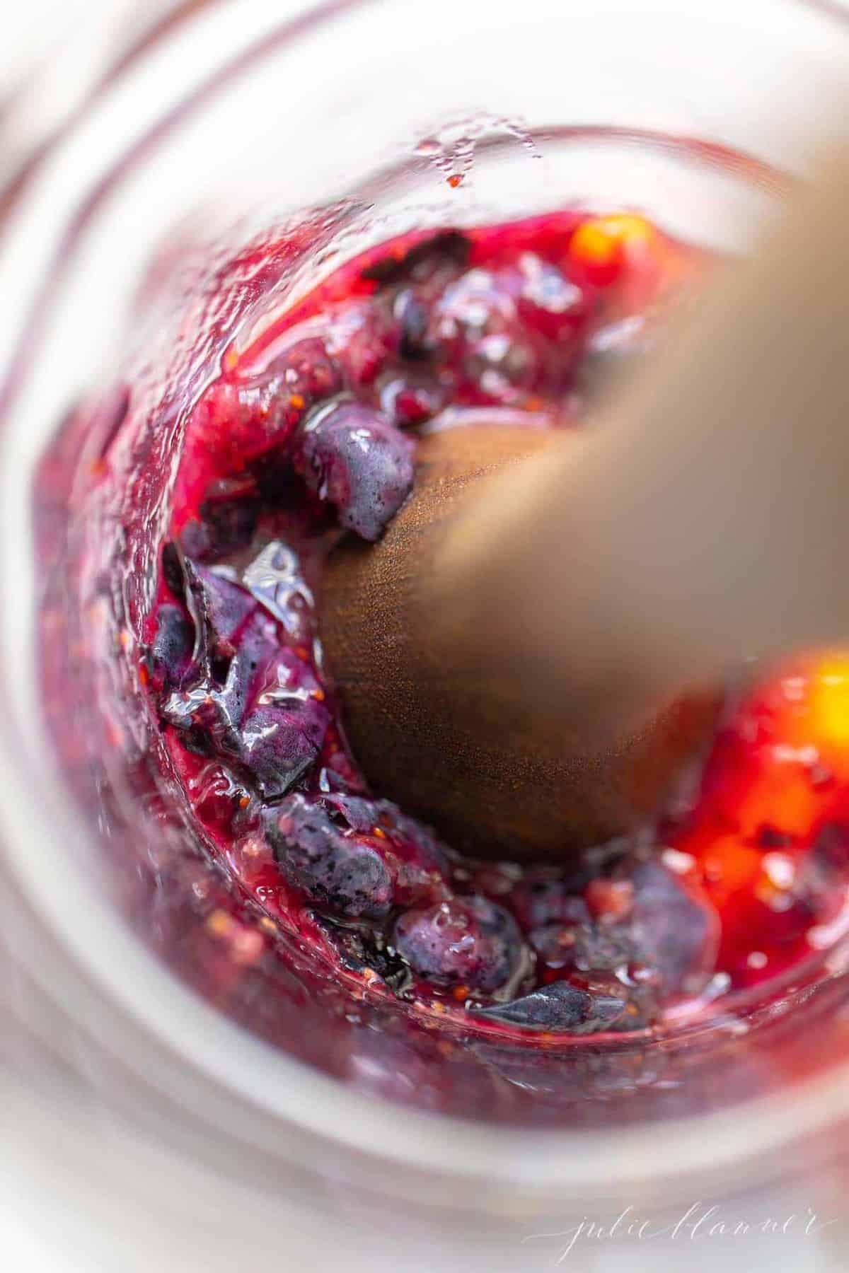 Looking into a pitcher of smashed fruit for a whiskey smash recipe, muddler at work.