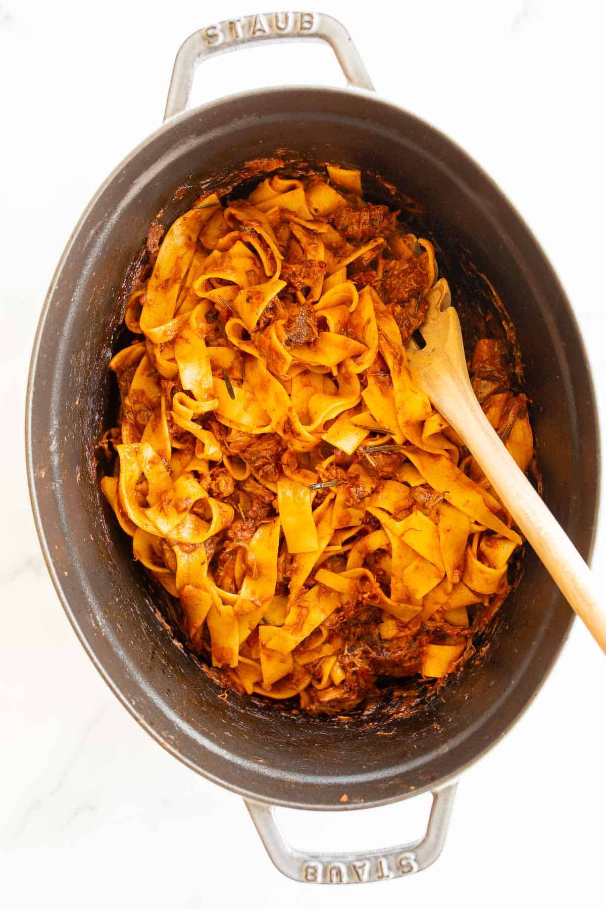 Beef ragu and Pappardelle pasta in a large cast iron pot, wooden spoon to the side.