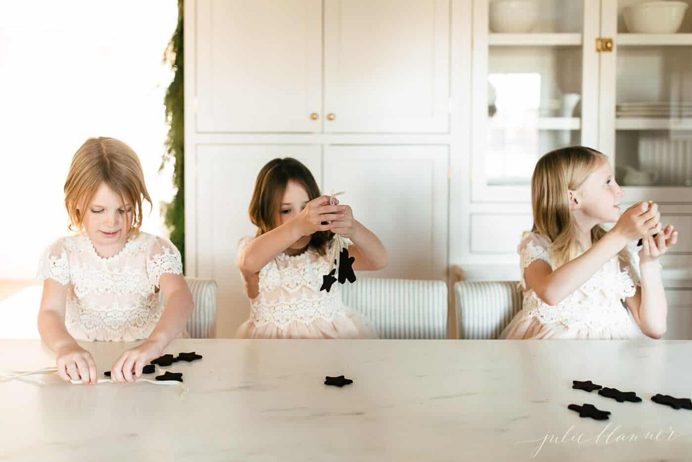 3 little girls threading ribbon through cinnamon applesauce ornaments.