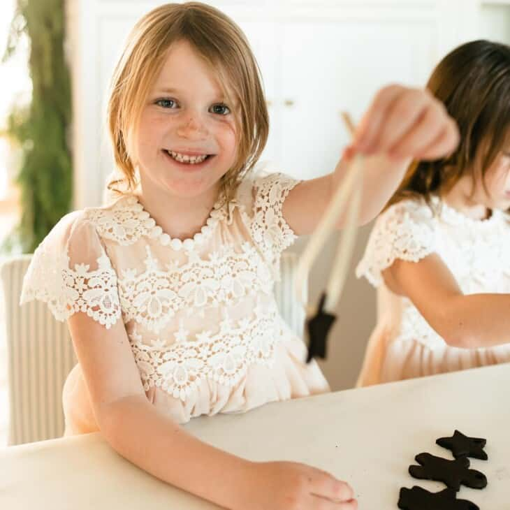 little girl threading ribbon through a cinnamon ornament.