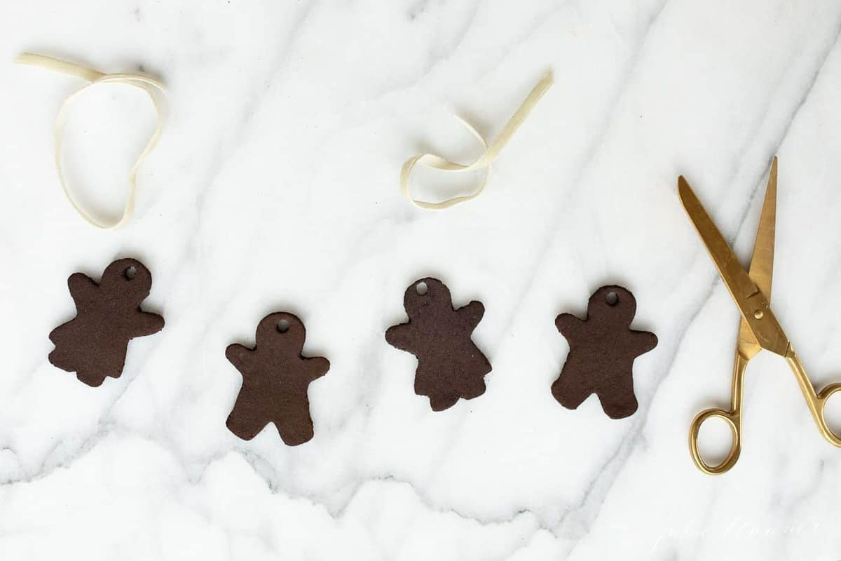 Marble surface, four gingerbread cinnamon ornaments with gold scissors to the side.