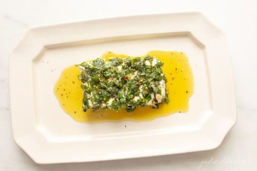 White platter with a cream cheese appetizer, marinated in herbs and oil.