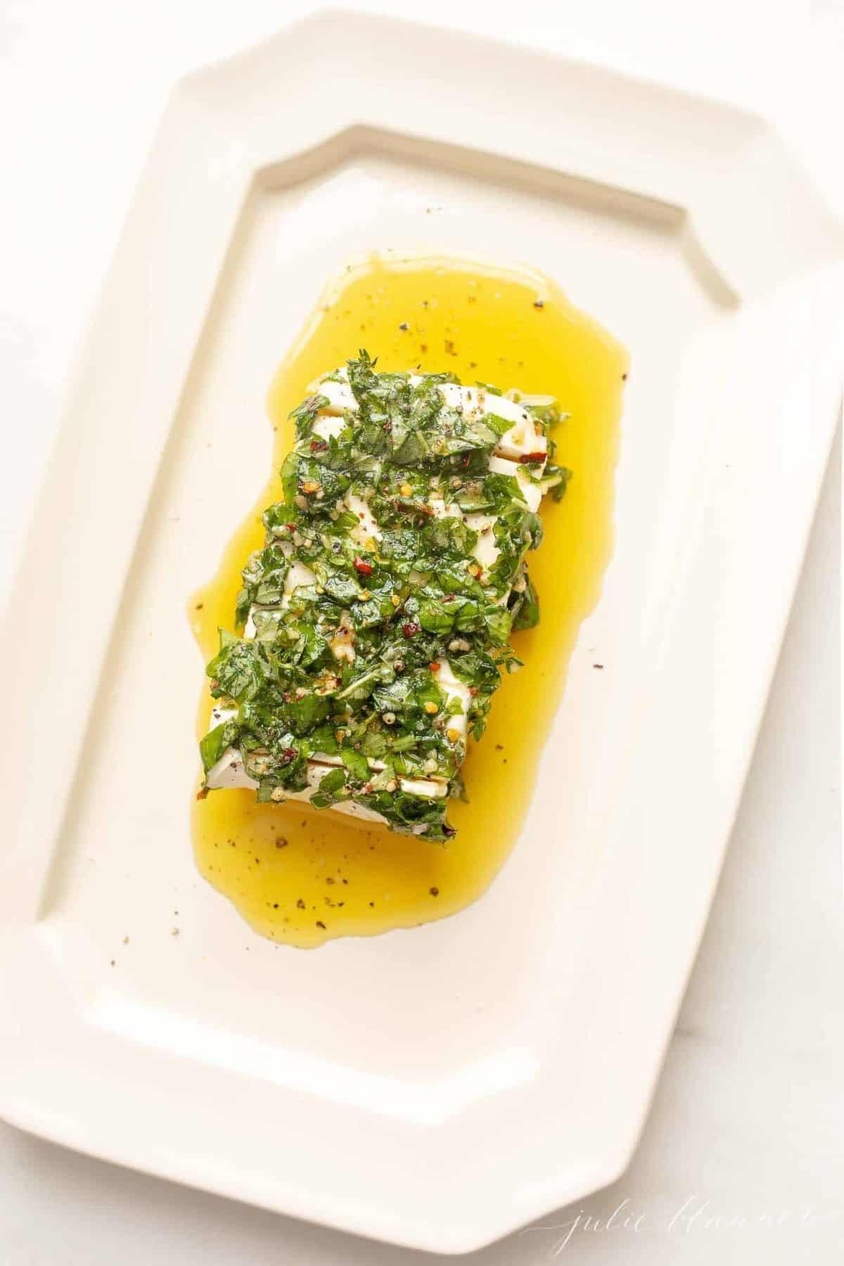 Prato branco com aperitivo de cream cheese, marinado em ervas e azeite.