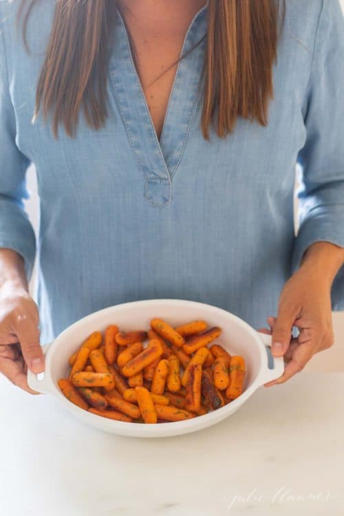 Woman in blue dress holding an oval baking dish filled with braised carrots.